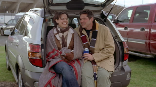 http://media.gettyimages.com/videos/couple-talking-while-sitting-in-open-trunk-of-car-at-tailgate-party-video-id1048-103?s=640x640