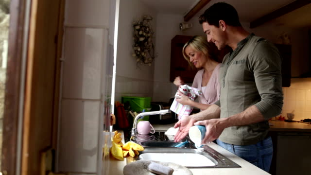 Couple talking whilst doing the dishes together