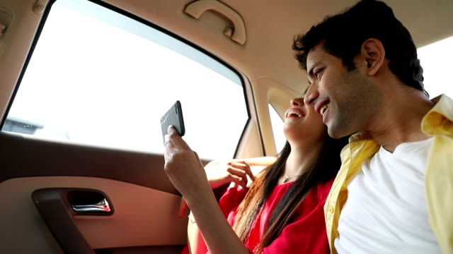 Couple using mobile phone in the car, Delhi, India