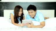 Couple Using Tablet On The Bed