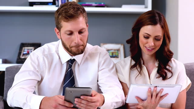 Couple using their tablets on the couch