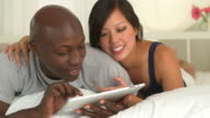 Couple using touch pad and laughing in bed