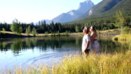 Couple wade into mountain lake at sunrise
