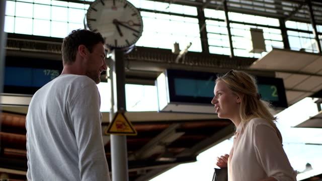 Paar wartet am Bahnhof