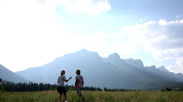 Couple walk across mountain meadow at sunrise