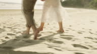Couple Walk Along Beach. Close Up Of Feet and Waves. Slow motion.