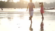 Couple walk along beach, take pic with digital tablet