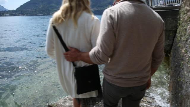 Couple walk down ramp to edge of lake, take picture