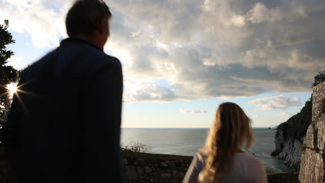 Couple walk down to stone wall overlook, look out