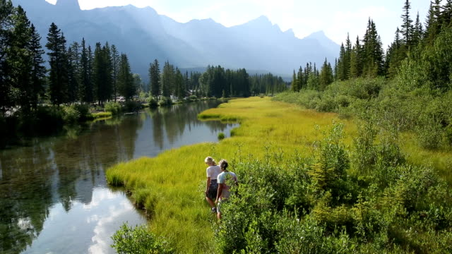 Couple walk through marsh to edge of mountain creek