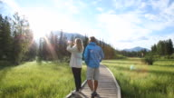 Couple walk through mountain meadow on boardwalk
