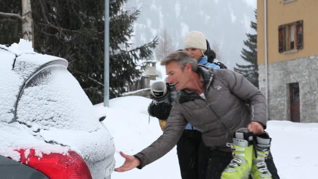 Couple walk to car in snowstorm, open rear door to stow gear