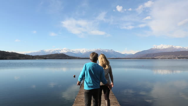 Couple walk to end of lake dock, look out to view