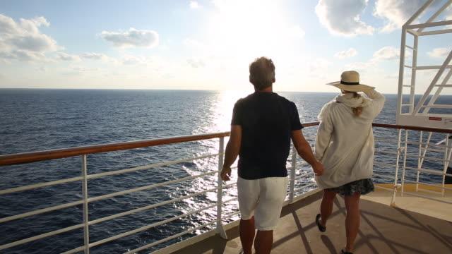 Couple walk to ship railing, looks off towards sunrise