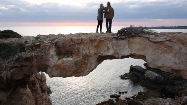 Couple walk to top of natural rock bridge, look out