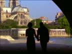 REAR VIEW SILHOUETTE couple walking along Seine under tunnel toward Notre Dame / Paris, France