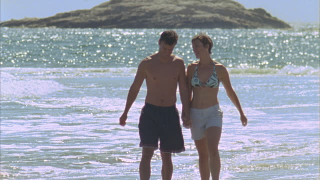 MS Couple walking along water's edge on beach then boy and girl run over / Phippsburg, Maine, USA