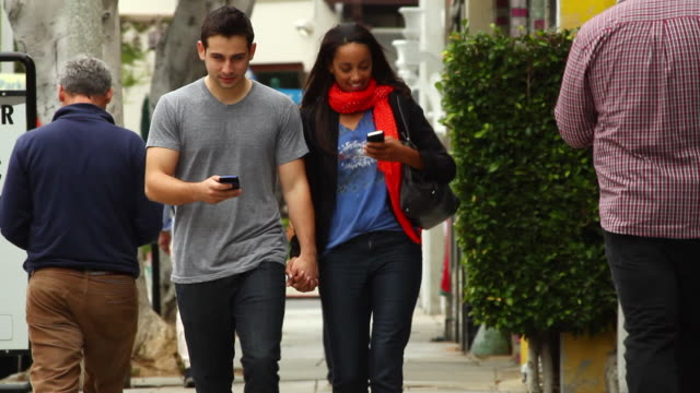MS Couple walking and texting on sidewalk / Santa Monica, California, United States