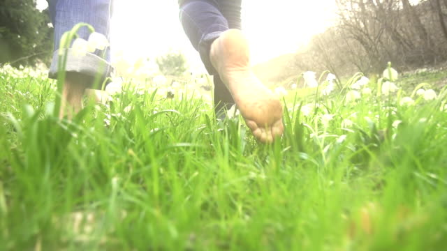 HD SUPER SLOW-MO: Couple Walking Barefoot Between Snowdrops