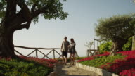 WS Couple walking down path,picking flower from flower bed / Ravello,Campania
