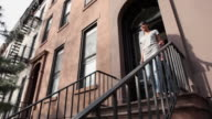 WS LA PAN Couple walking down stoop of apartment building / Brooklyn, New York City, USA