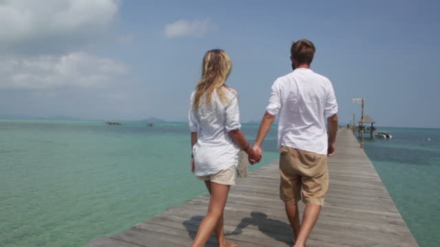 Couple walking on jetty by the beach