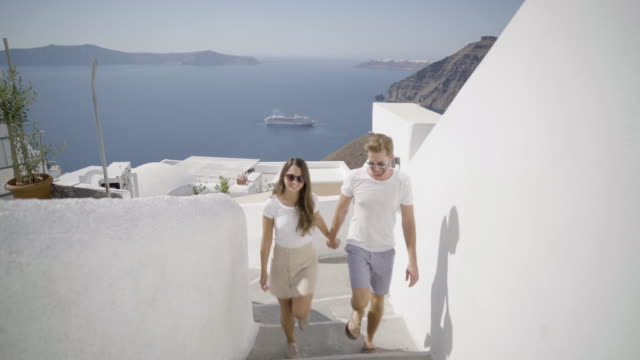 couple walking on narrow path through greek village