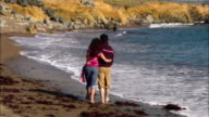 MS, Couple walking on rocky beach, rear view, Moonstone Beach, Cambria, California, USA