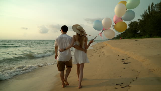 Couple walking on the beach. Young happy interracial couple walking on beach smiling holding around each other. Asian woman, Caucasian man.