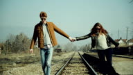 Couple walking on the rail tracks