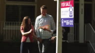 MS PAN Couple walking with real estate agent, woman placing 'sold' sticker on sign outside house / Provo, Utah, USA