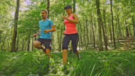 SLO MO Couple warming up before start running through the forest