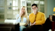 Couple watching TV together and crying