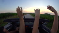 HD SLOW MOTION: Couple Waving While Driving In Convertible