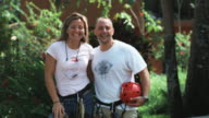 couple wearing harnesses about to go on a zip line tour through the Costa Rican rainforest