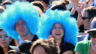 MS Couple wearing wigs in stadium crowd clapping during sporting event