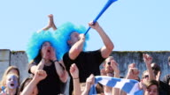 MS Couple wearing wigs standing in crowd cheering during soccer match man blowing vuvuzela