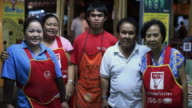 MS Couple who own restaurant with three employees posing and smiling inside restaurant /  Vang Vieng, Vientiane, Laos