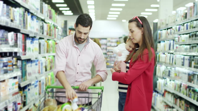 Couple with baby girl in shopping in supermarket