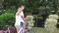 Couple with bicycle walking in the park