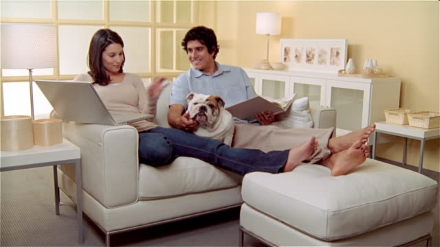 MS, Couple with Bulldog relaxing in living room, woman using laptop, man reading
