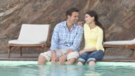 Couple with legs dangling in swimming pool