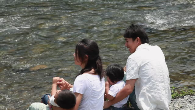MS HA Couple with son (6-7) and daughter (2-3) sitting on edge of river / Tokyo, Japan