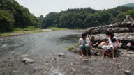 WS Couple with son (6-7) and daughter (2-3) sitting on rocks by river / Tokyo, Japan
