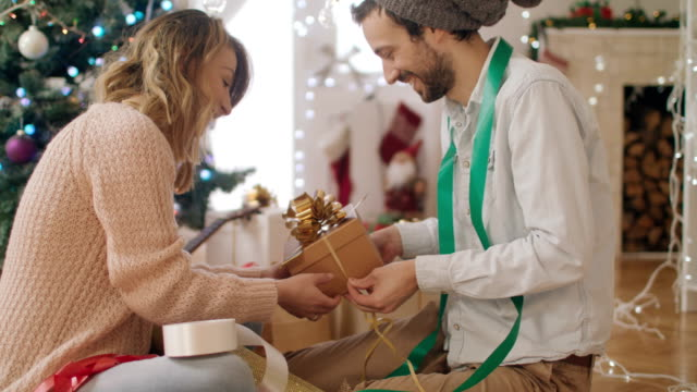 Couple wrapping gifts for Christmas 4K