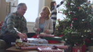 MS Couple wrapping Xmas gifts while daughter decorating tree in background  / Rutland,Vermont, USA