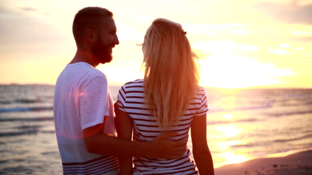 Couples hugging by the beach at sunset
