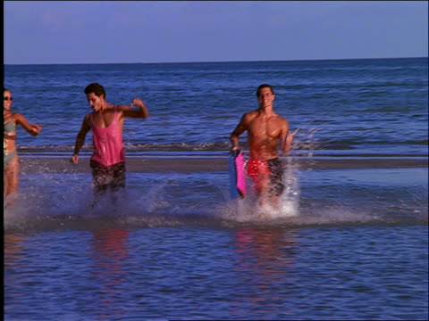 2 couples in swimsuits running in water on beach