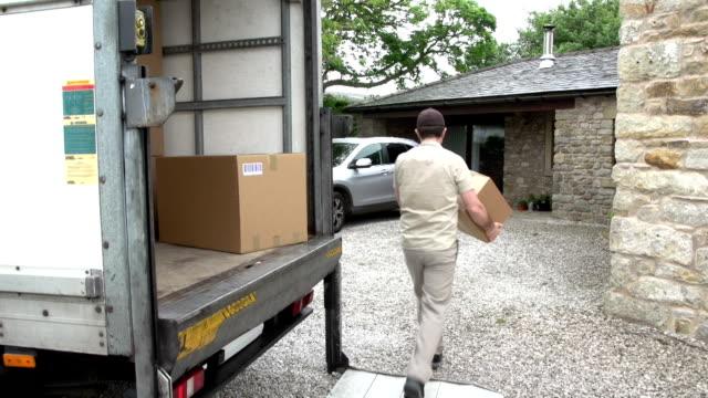 Tariffa corriere/consegna uomo dando un pacchetto di una casa