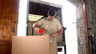 Courier / Delivery man Taping up box in Warehouse